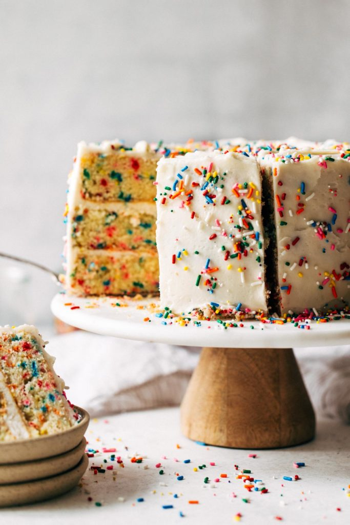 a sliced funfetti layer cake on a cake stand