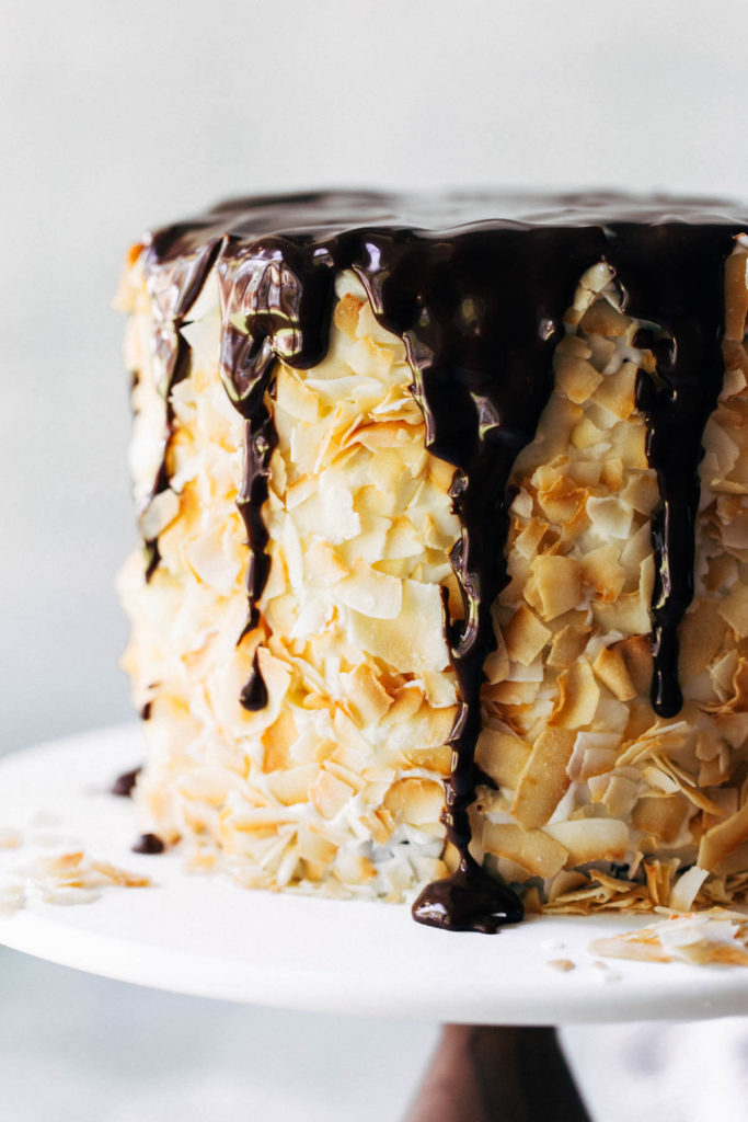 a layer cake covered in coconut with chocolate dripping down the sides