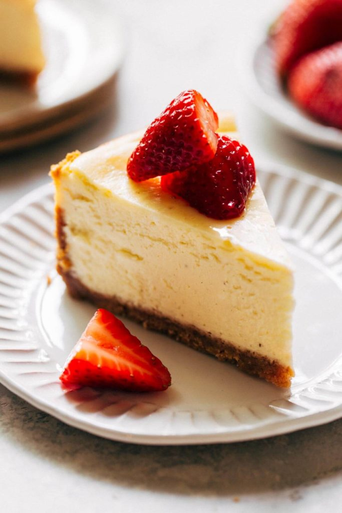 a slice of cheesecake on a plate with strawberries