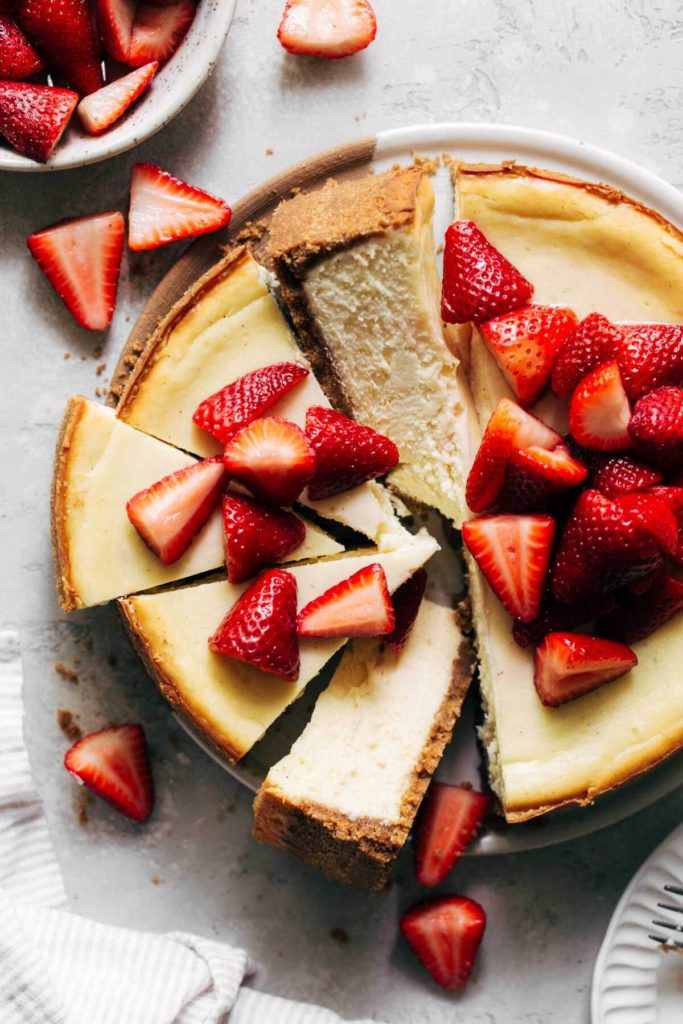 the top of a baked cheesecake topped with strawberries