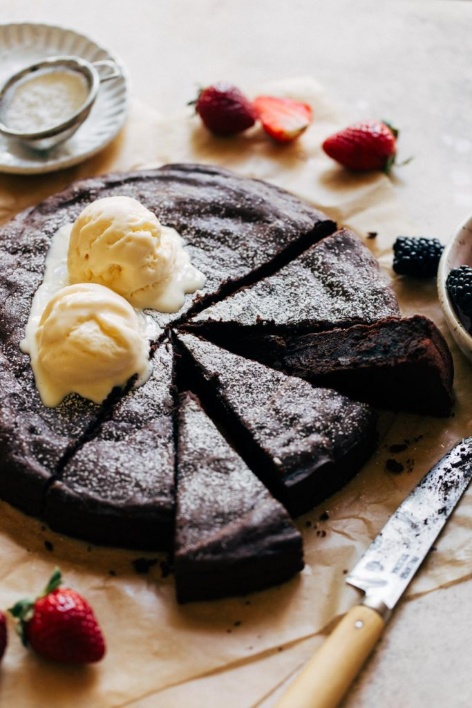 flourless chocolate cake sliced on parchment paper