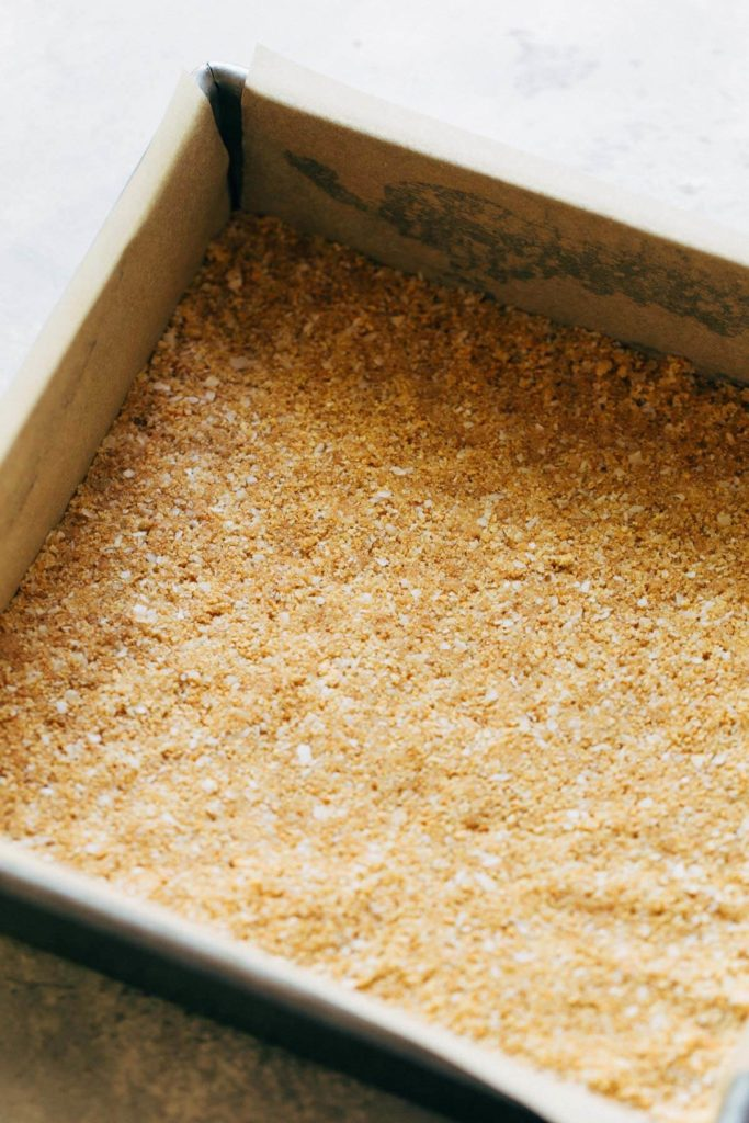 a graham cracker crust pressed into a square baking dish