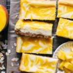 slices of mango cheesecake bars scattered in a cooling rack