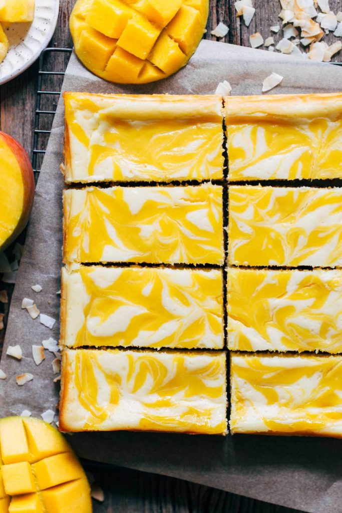 a cooling rack of slices of coconut mango cheesecake bars