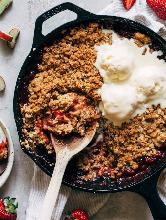 strawberry rhubarb crisp baked in a cast iron and topped with ice cream