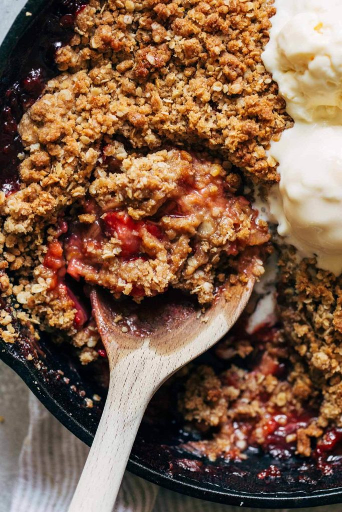 close up on a spoon full of strawberry rhubarb crisp