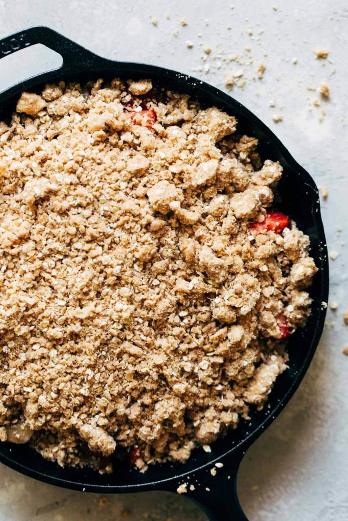 crumble topping sprinkled on top of fresh strawberries and rhubarb