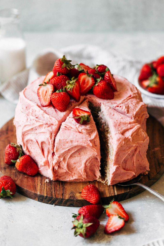 sliding out a slice of strawberry cake from the entire cake