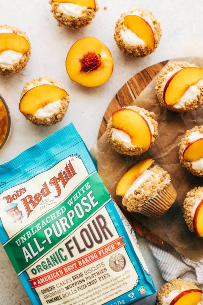 peach cupcakes scattered around a bag of flour