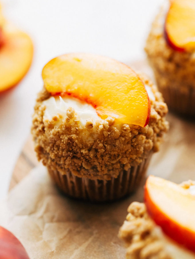 close up on a cupcake topped with a fresh peach slice