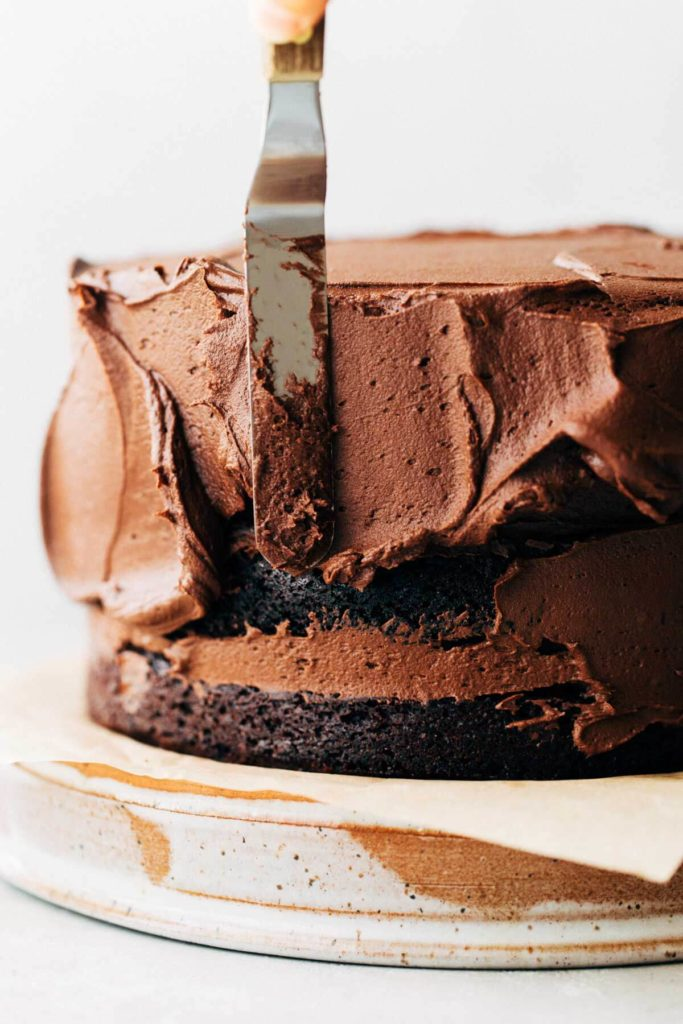 spreading chocolate frosting onto a layered chocolate cake