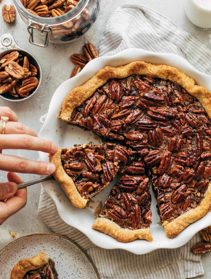 lifting a slice of pecan pie out of the pie dish