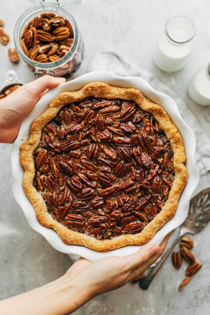 holding a freshly baked pecan pie