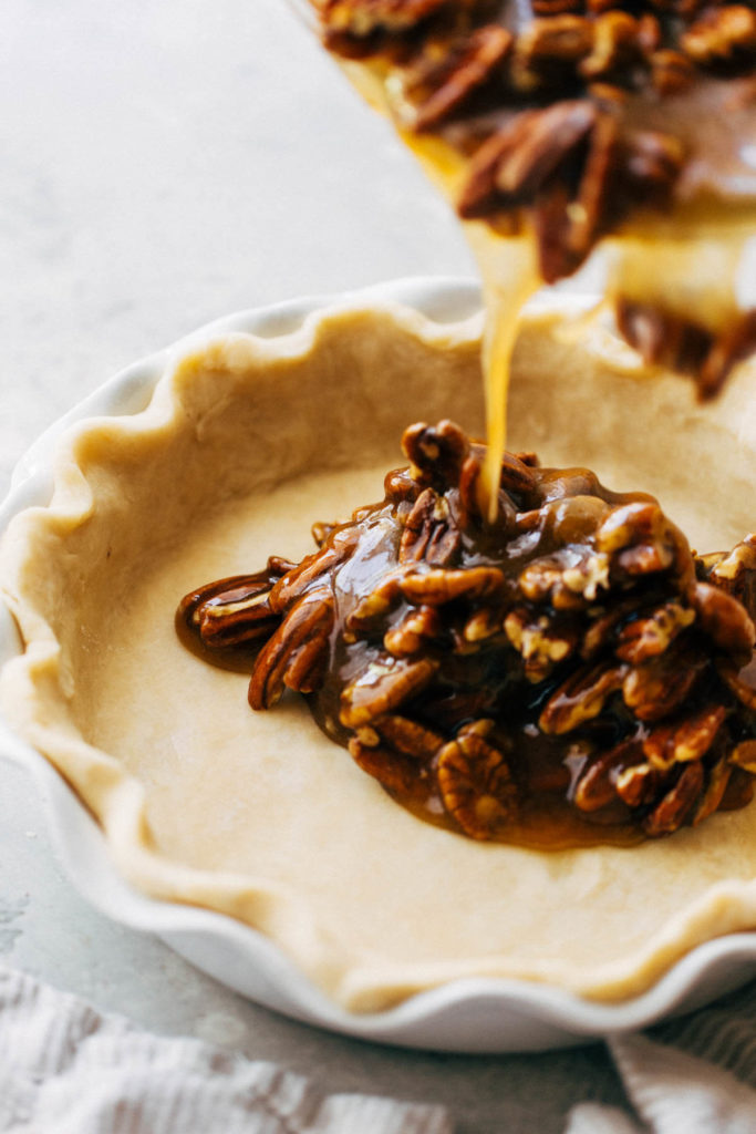 pouring pecan pie filling into a homemade pie shell