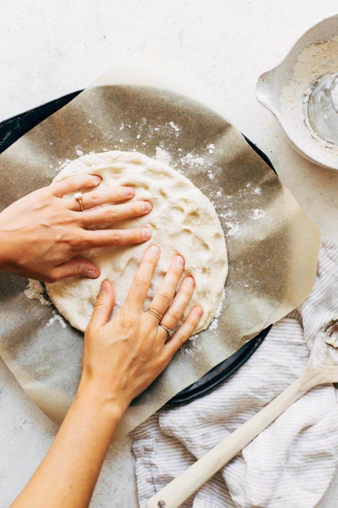 pressing pizza onto a round baking pan
