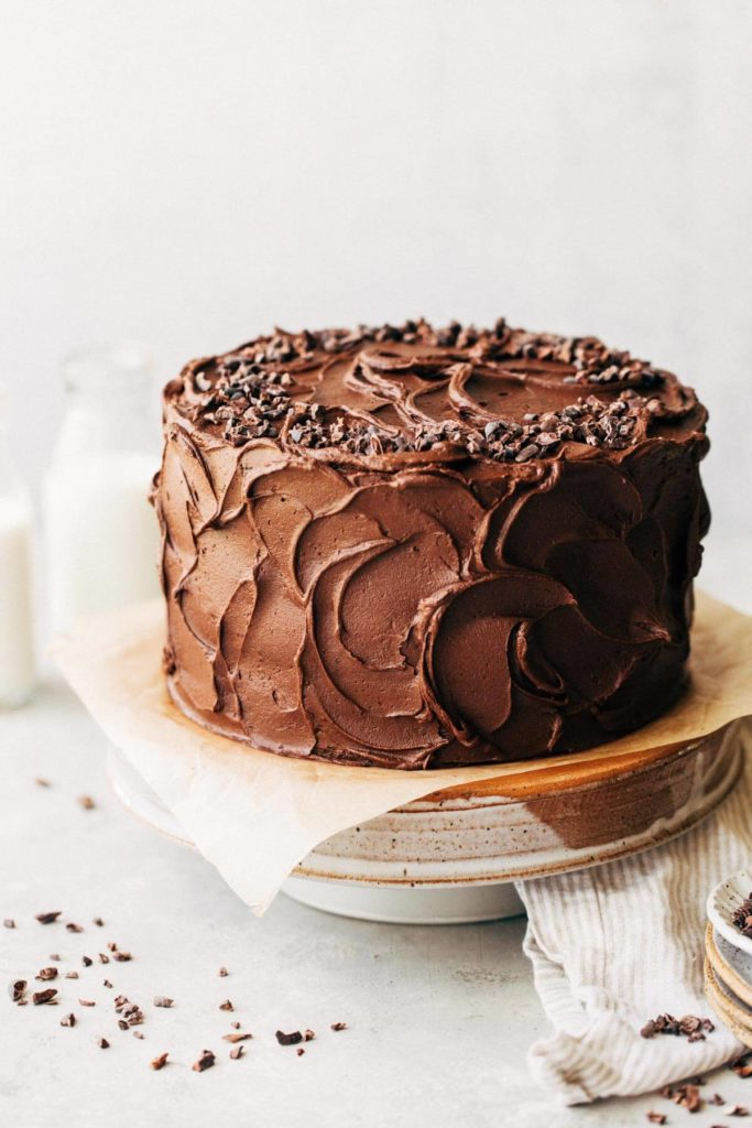 chocolate cake with swirled chocolate frosting sitting on a cake stand