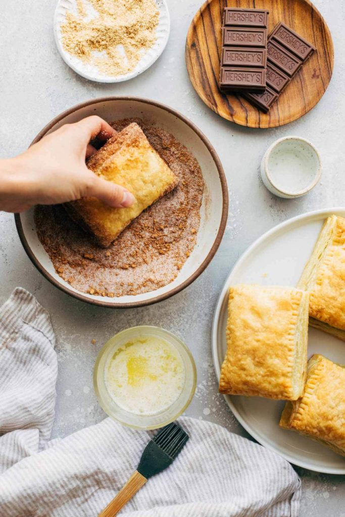tossing puff pastry in a bowl of cinnamon sugar