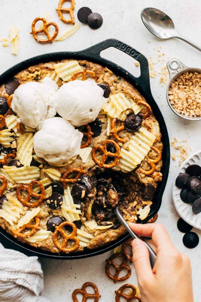 digging a spoon into a giant skillet cookie filled with pretzels, potato chips, and chocolate