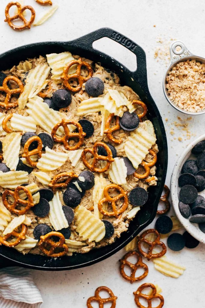 cookie dough pressed into a cast iron skillet and topped with pretzels, potato chips, and chocolate