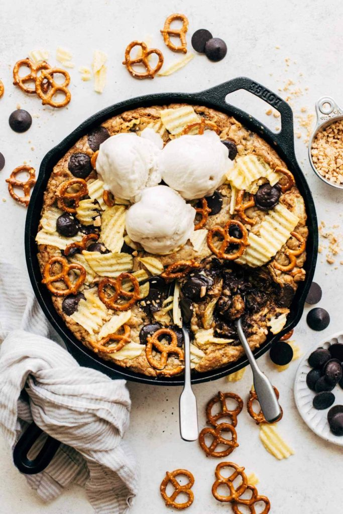 an overhead view of a compost skillet cookie with potato chips, pretzels, chocolate, and ice cream on top