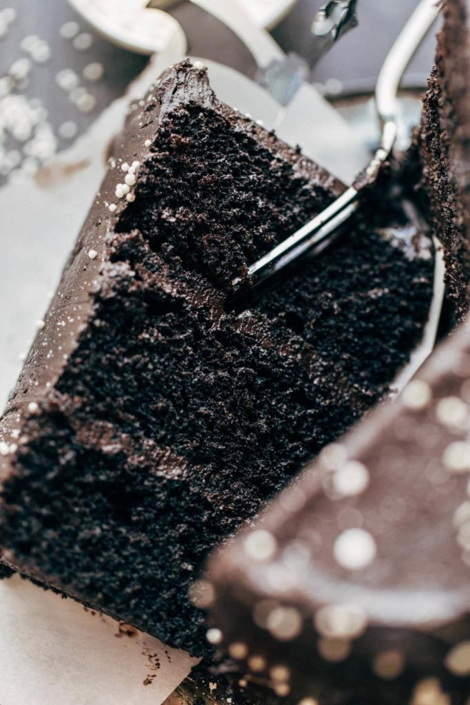 digging a fork into a slice of black velvet cake