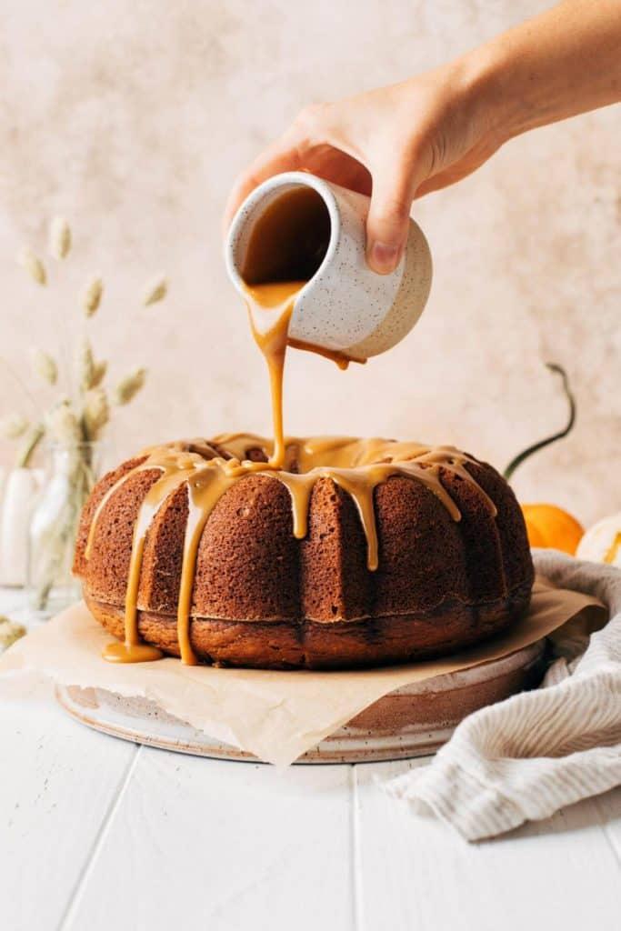 pouring butterscotch sauce on top of a pumpkin bundt cake