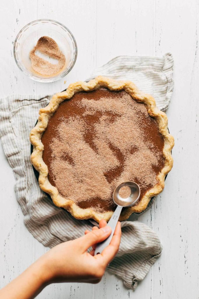 dusting the top of an apple butter pie with cinnamon sugar
