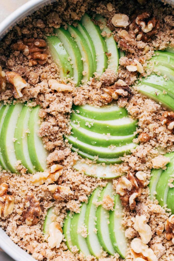 close up on the top of an apple cake topped with apple slices and crumble topping, before it's baked