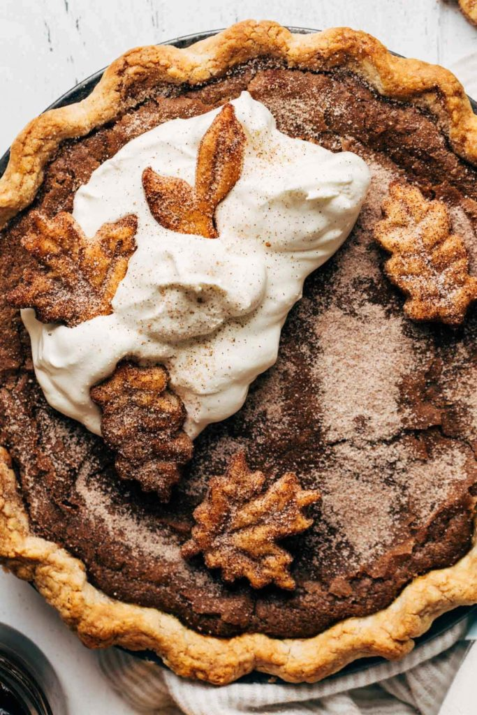 close up on the top of an apple butter pie topped with whipped cream