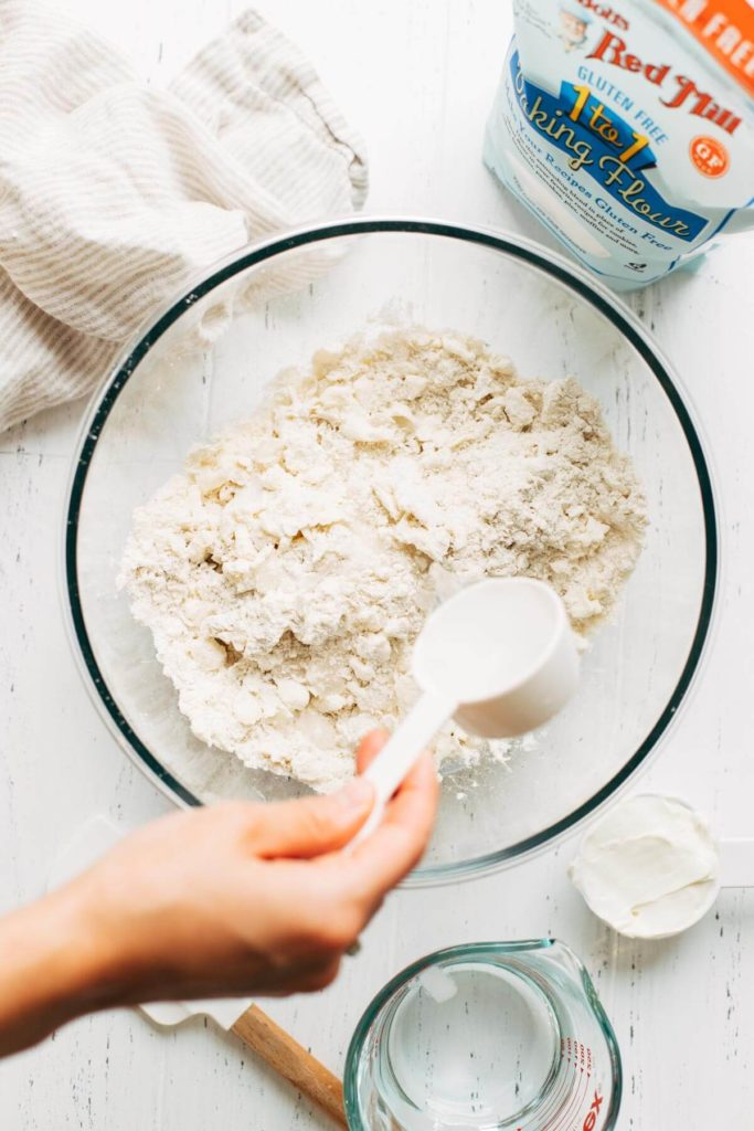 pouring water into pie dough
