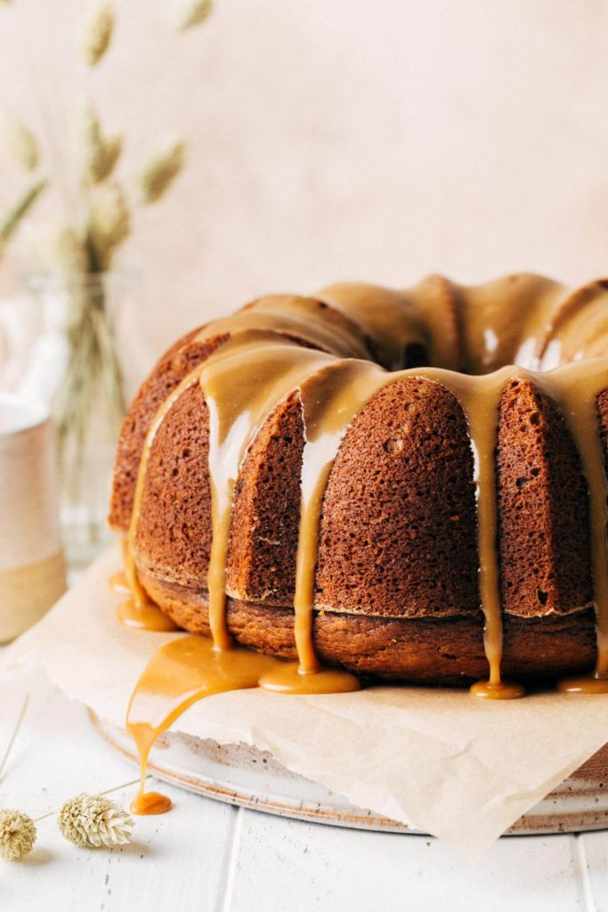 close up on the side of a pumpkin bundt cake with butterscotch sauce dripping down the sides