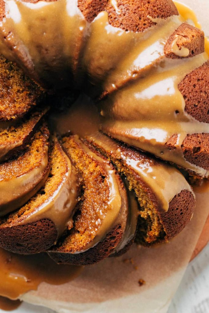 close up on the top of a pumpkin bundt cake with slices laying in their sides