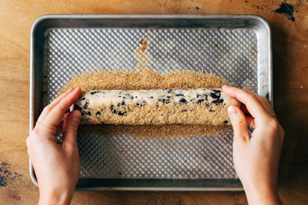 rolling a log of chilled shortbread cookie dough in coarse sugar