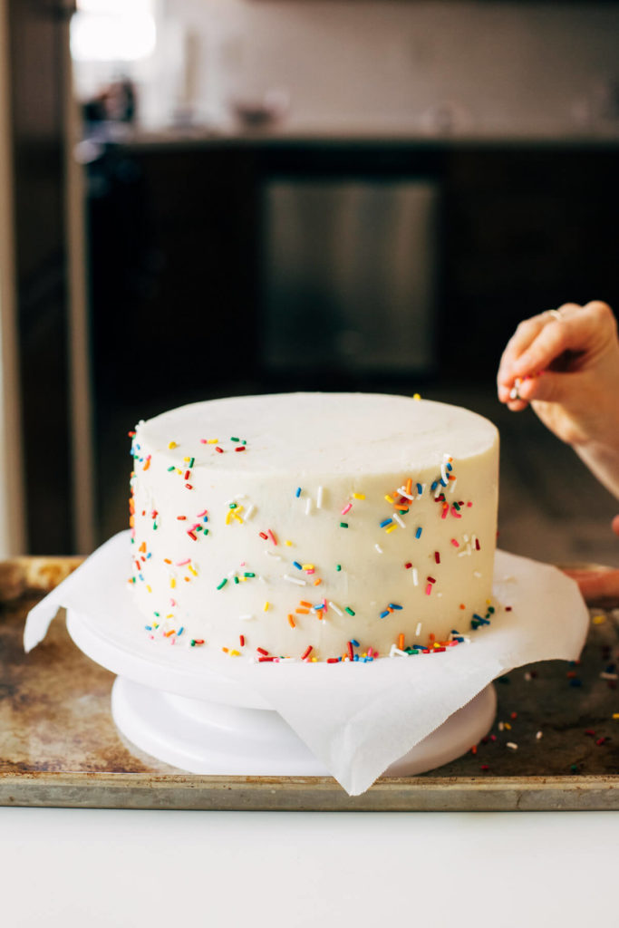 tossing sprinkles at the sides of a layer cake