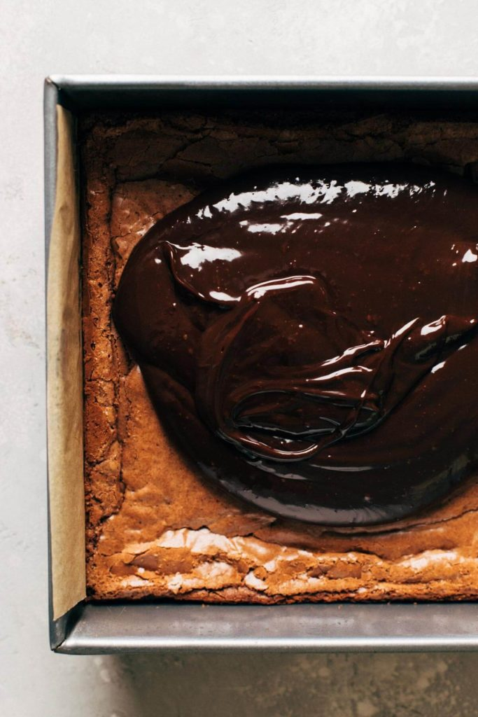 a pool of chocolate ganache poured on top of baked brownies