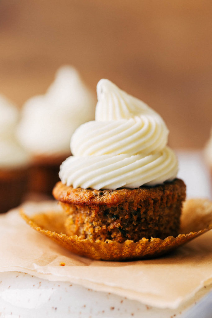 a cupcake with cream cheese frosting piped on top