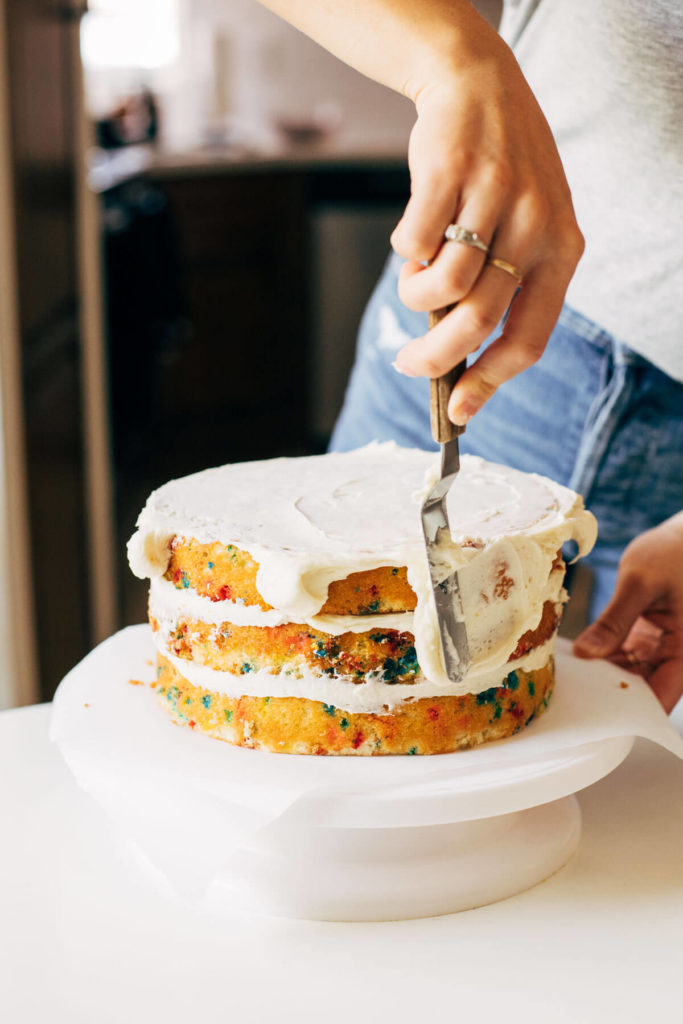 spreading buttercream on the sides of a cake