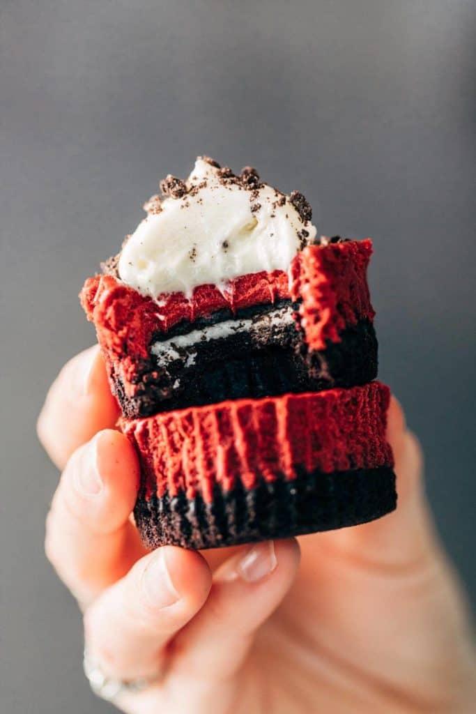 holding two mini red velvet cheesecakes
