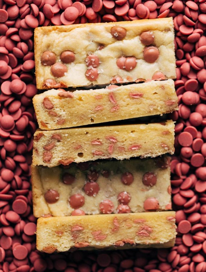 slices of shortbread resting in a bed of ruby chocolate chips