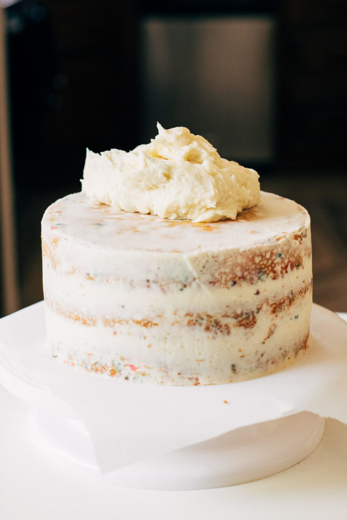 crumb coated cake with a dollop of buttercream on top