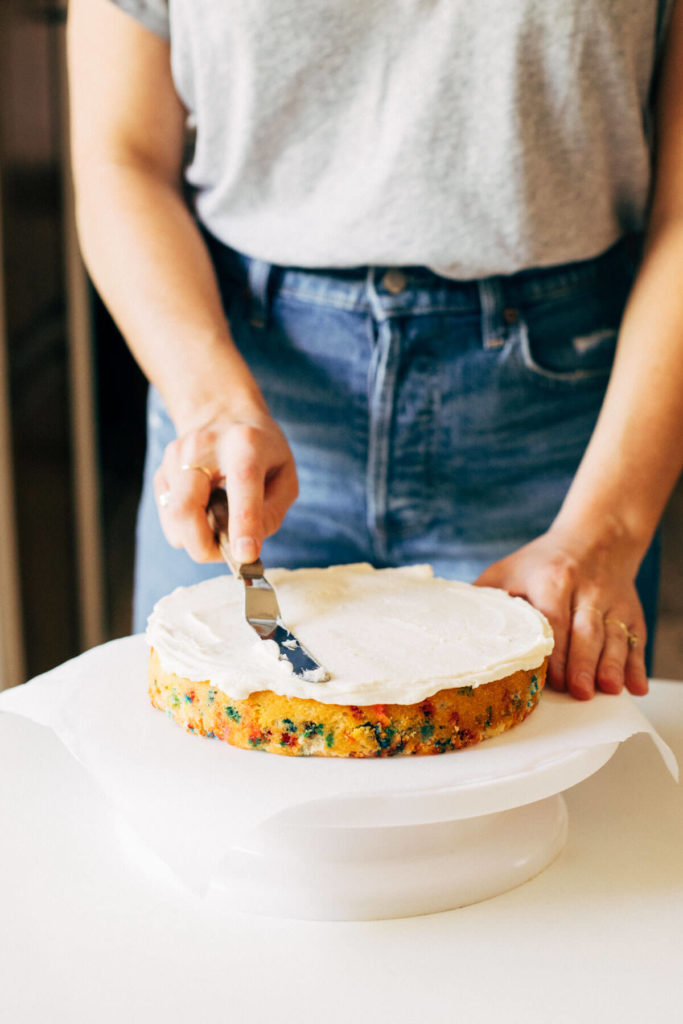spreading buttercream between cake layers