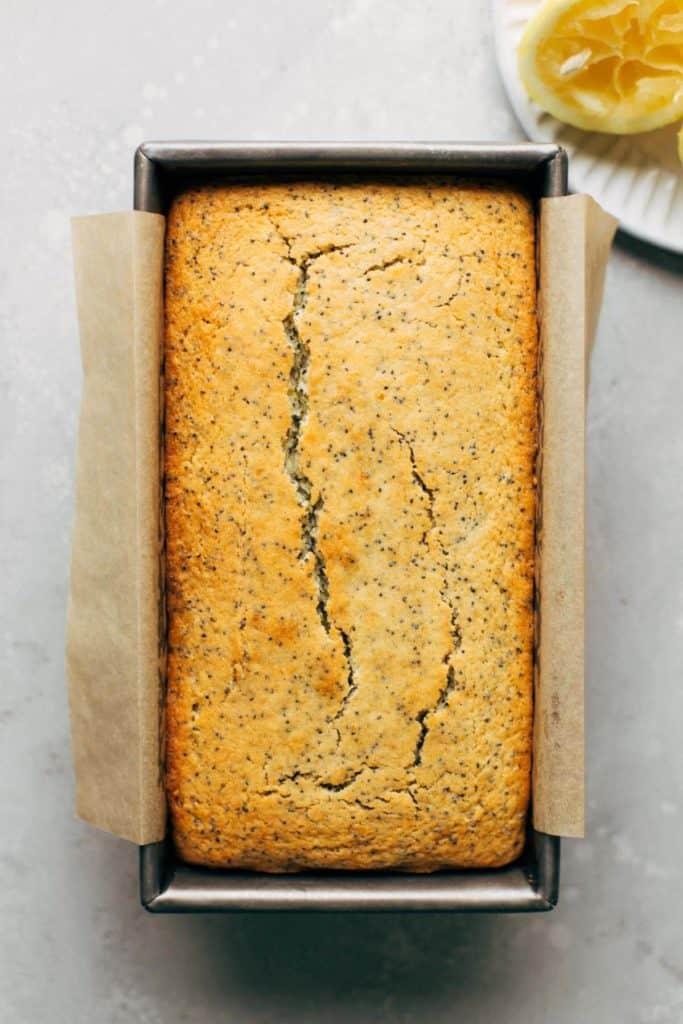 freshly baked lemon poppy seed bread in a loaf pan