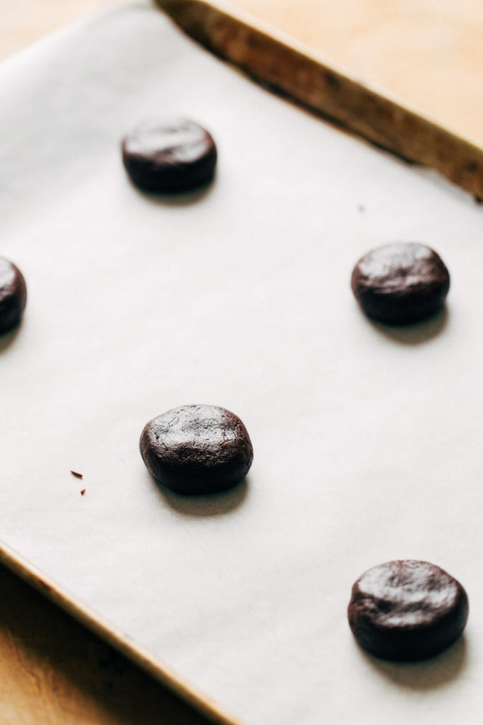 scooped chocolate cookie dough arranged on a baking sheet