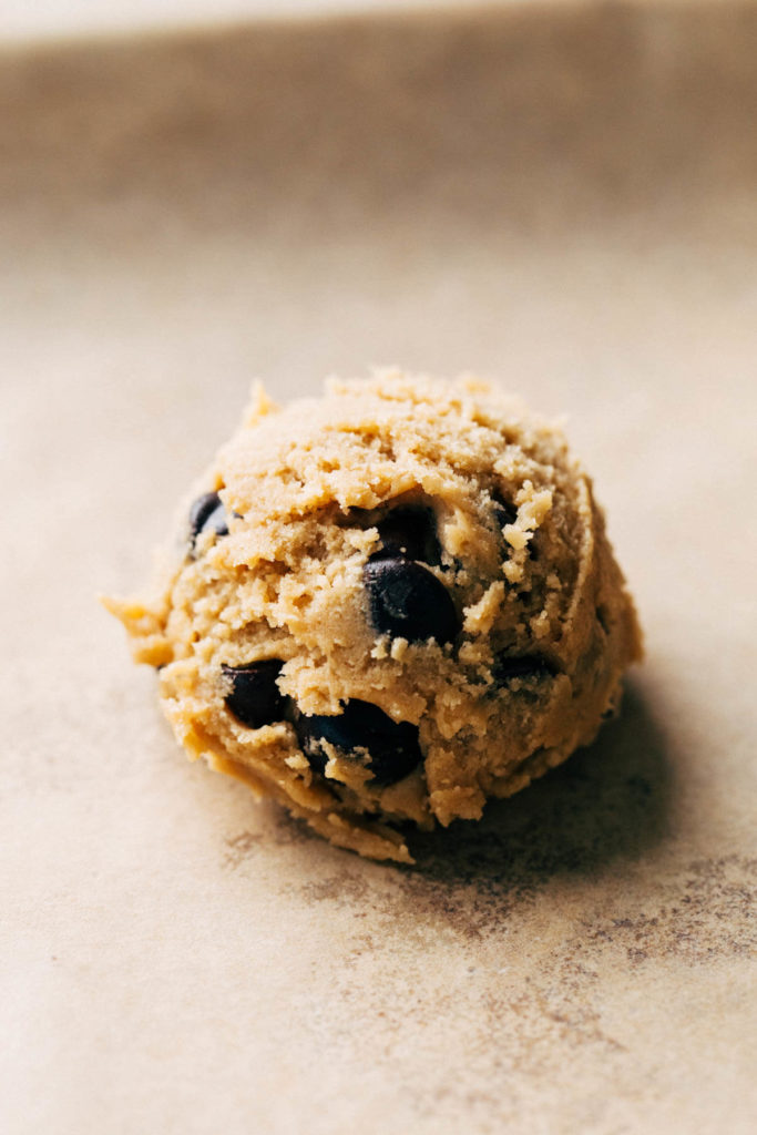 close up on a ball of scooped cookie dough on a baking sheet