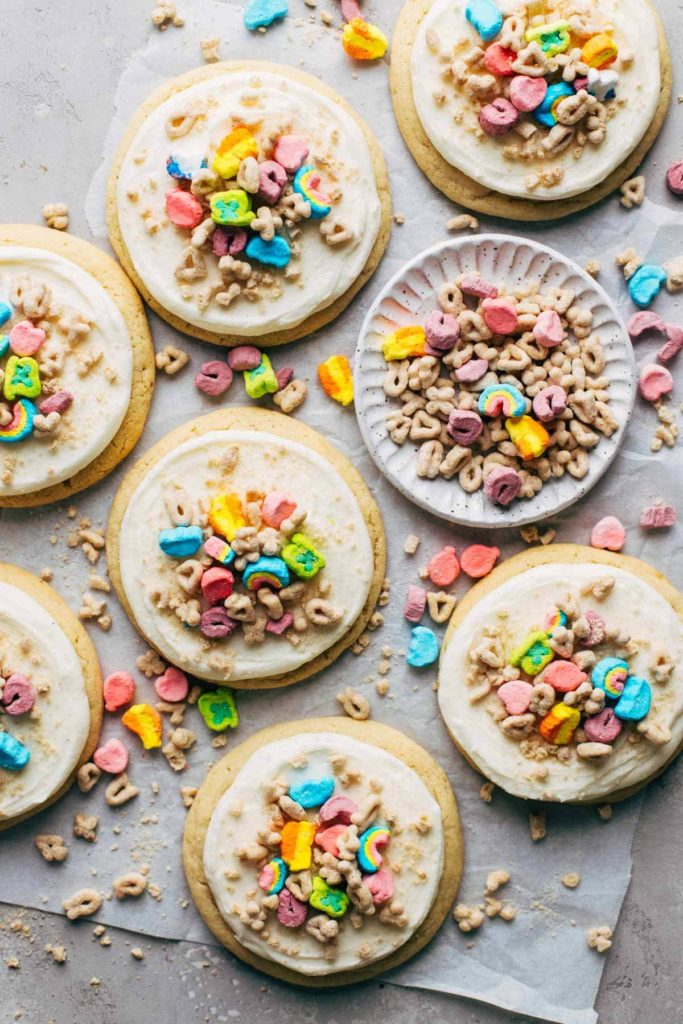 the top view of sugar cookies topped with frosting and Lucky Charms cereal