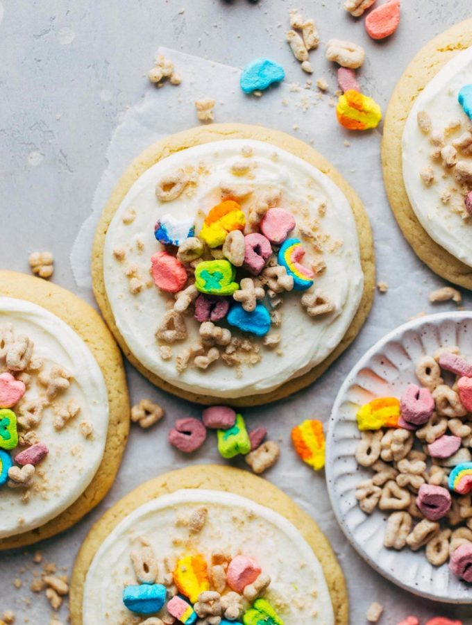 the top view of a sugar cookie topped with frosting and Lucky Charms cereal
