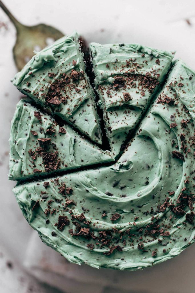 the top view of a mint chocolate chip layer cake with a buttercream swirl