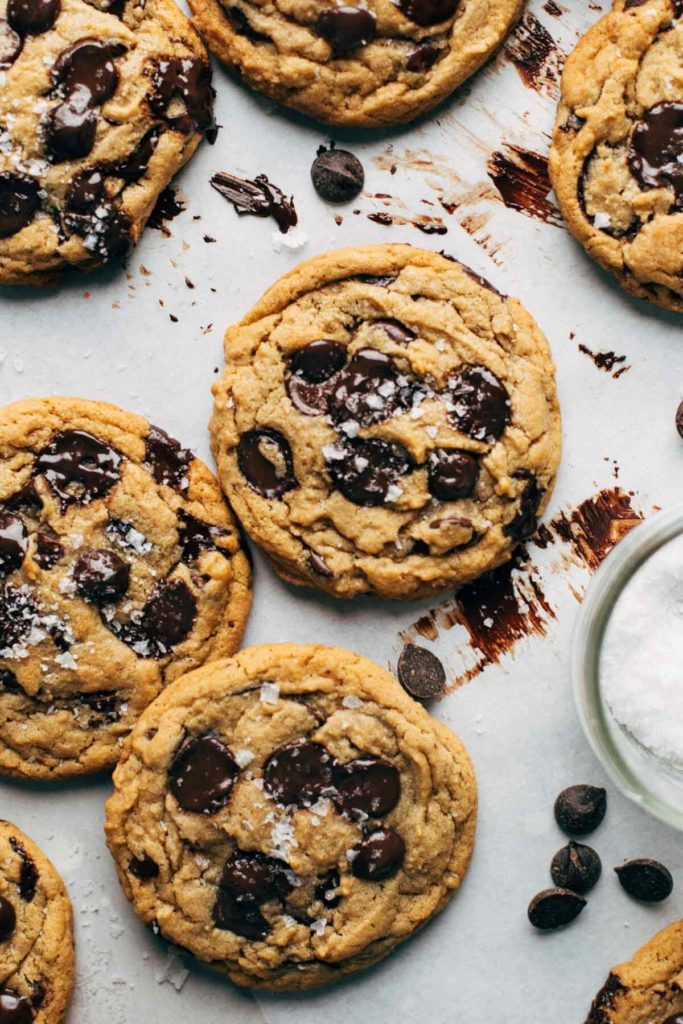 vegan chocolate chip cookies scattered on parchment paper