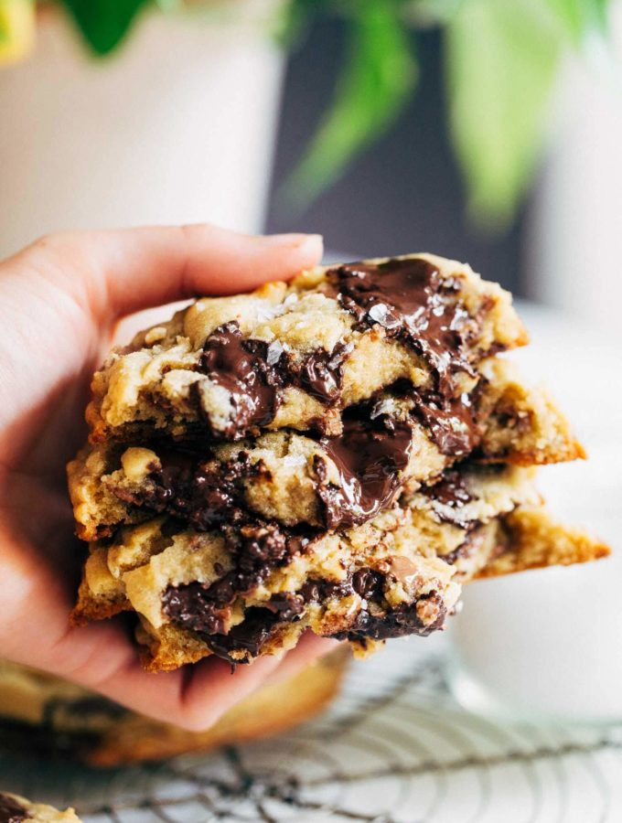 holding a stack of gooey bakery style chocolate chip cookies