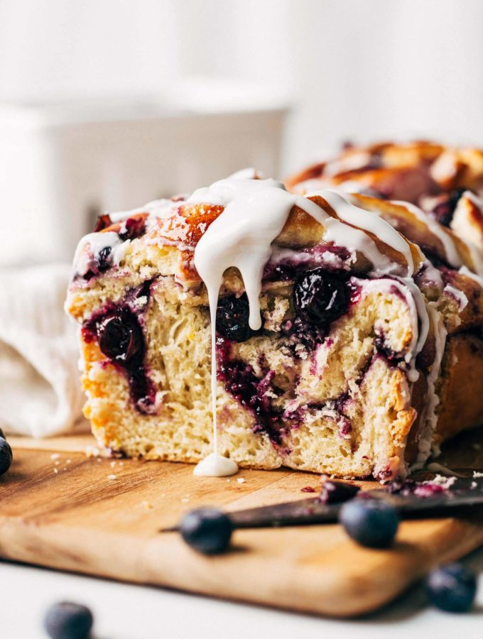 icing dripping down the side of a blueberry babka